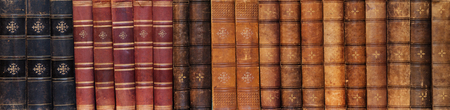 Long row of ancient books on shelf in the library