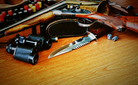 Hunting equipment: gun, knife, bullet, cartridge belt, binoculars and horn are on a wooden background Stock fotó