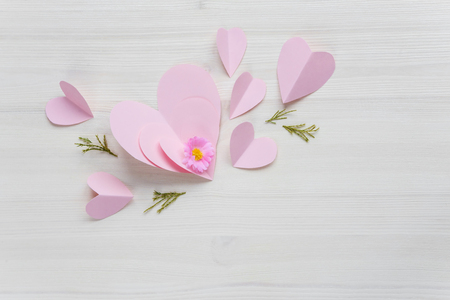 Spring gentle romantic composition with flower and pink paper hearts on white wooden background. Beautiful background or greeting card for Valentine's Day ore wedding invitation, with copy space