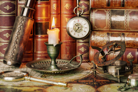 Vintage concept of discoveries: traveler accessories (antique spyglass, magnifier, sundial, compass), pocket watch and burning candle in an old candlestick are on the background of antique books