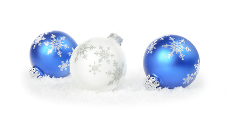 White and blue Christmas balls with a snowflakes are on a white snow isolated on white background