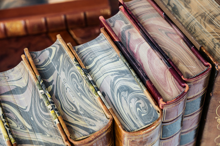 Row of antique books in a leather hardcover close-up, top view