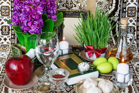 Tabletop with Haft-seen elements for Nowruz: sonbol (hyacinth), sabzeh (grass), seeb (apple), somaq (sumac powder), seer (garlic), serkeh (vinegar), goldfishes, flowers hyacinths, coins, burning candles, painted eggs and mirror