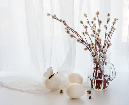 Easter greeting card. Fluffy pussy-willow branches in a transparent glass pitcher and three white Easter eggs against a white transparent cloth