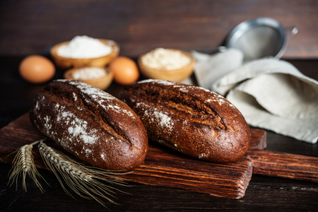 Two loaves of rye homemade bread, a gray linen napkin, flour and grain in wooden bowls, eggs and spikelets are on a dark wooden background