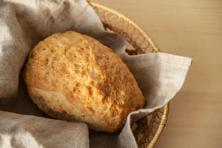 Fresh homemade gluten-free bread ciabatta in the wickers basket with linen napkin, wish copy-space. Ciabatta is tradition italian bakery product