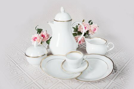 White crockery for coffee: coffeepot, cup, serving plate and sugar bowl as well as rose flowers are on a beautiful tablecloths