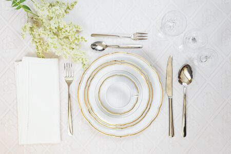 Beautifully decorated table with white plates, crystal glasses, linen napkin and cutlery are on luxurious tablecloths; top view