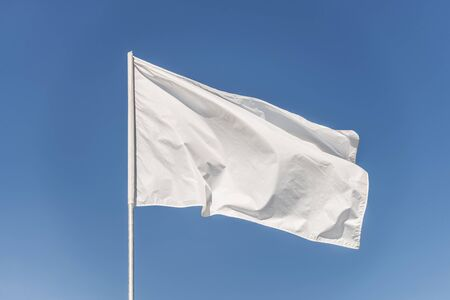 White flag against the blue sky fluttering in the wind