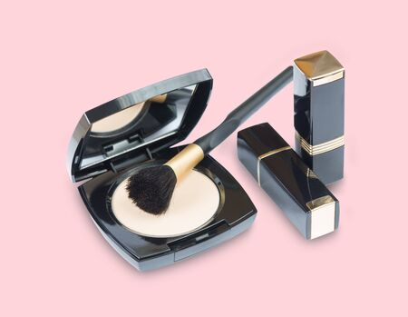 Beige pressed powder in a box with a mirror, brush and lipstick isolated on a pink background 스톡 콘텐츠