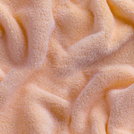 Pink fluffy terry towel laid in waves, close-up as seamless pattern ore background