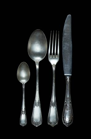 Row of vintage knife, fork and spoons are isolated on black background Stockfoto