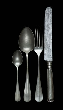 Row of vintage pewter knife, fork and spoons are isolated on a black background