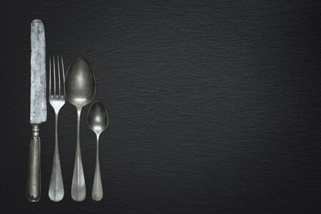 Row of vintage pewter knife, fork and spoons are on a black slate background, with copy-space Stockfoto