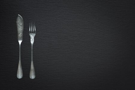 Vintage fork and knife for fish are on a background of slate stone, with copy-space