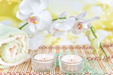 Spa concept: bath towels, two lighted candles and a branch of white orchid