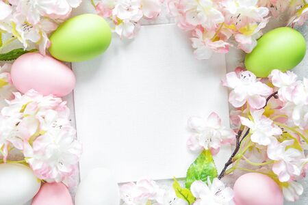 Beautiful delicate Easter frame with pink cherry flowers and multicolored Easter eggs