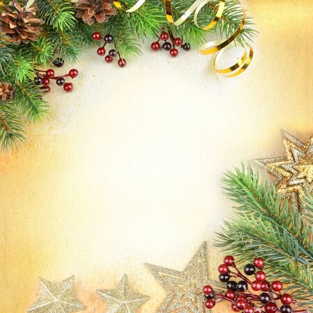 Christmas compositionon with green spruce branches, cones, red holly berries, sparkling stars and golden serpentine on a background of old paper