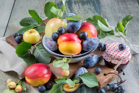 Several red nectarines with green leaves, blue plums and prunes in a enamelled bowl on the old wooden table
