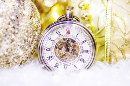 Festive Christmas still life with a pocket watch, a gift box and shiny Christmas decorations in golden tones Stock Photo