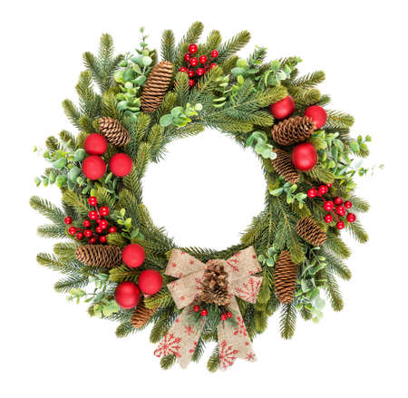 Traditional rustic Christmas wreath of green spruce and eucalyptus branches, decorated with red holly berries, red christmas baubles, spruce cones and bow, isolated on a white background