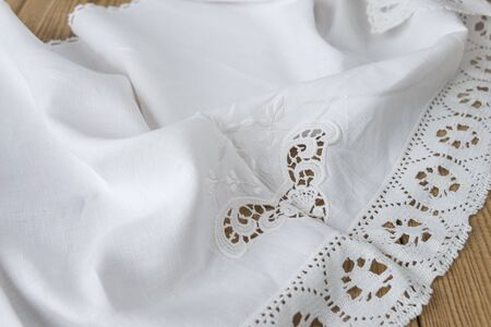 White natural cotton fabric with embroidery and lace with soft folds lies on an old wooden table