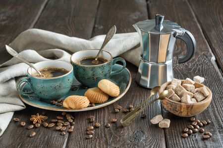 Two blue vintage cups of black coffee, cookies and geyser coffee maker surrounded by gray linen napkins, sugar pieces and coffee beans on old wooden table