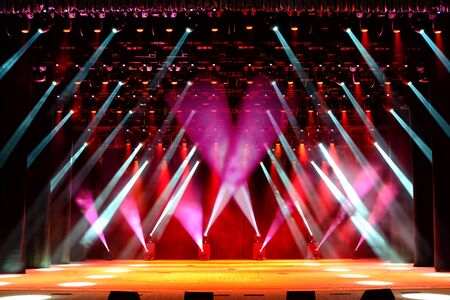 Illuminated empty show stage with red light beams and stage fog