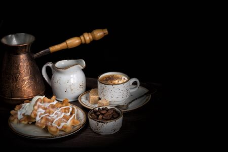 Cup of coffee, waffles, ice cream, coffee maker and coffee beans are on a dark background, with copy space