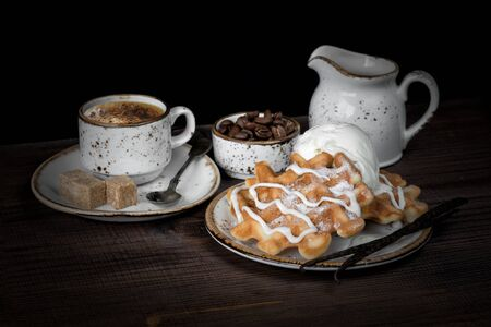Cup of coffee, waffles and coffee beans are on a dark background