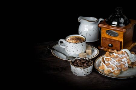 Cup of coffee, waffles, ice cream, coffee mill and coffee beans are on a dark background, with copy space