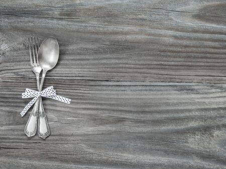 Crossed vintage forks and spoons, tied with a ribbon with polka dots, on the gray background of old wooden boards; with space for text