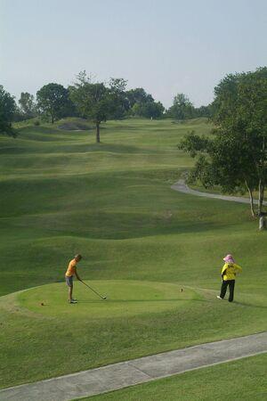 caddie: Female golf player before tee-off at par-5 golf hole