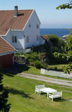 White, wooden house in a garden near the sea in Loshavn near Farsund in Vest-Agder, Norway. photo