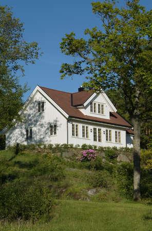 White, wooden villa in green, lush garden Stock Photo - 488600