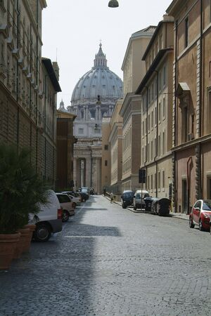 st peter: Local street in Rome with the dome of the St. Peter Cathedral in the background