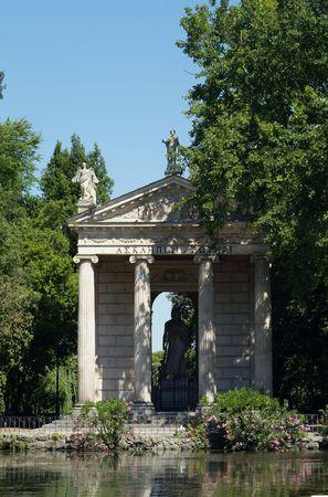 aesculapius: Stile tempio greco con una statua del dio Aeklepios (Esculapio), su un'isola nello stagno in giardino di Villa Borghese, Roma, Italia.