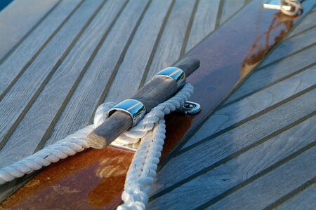 cleat: Cleat and rope on a wooden sailboat with teak-deck Stock Photo