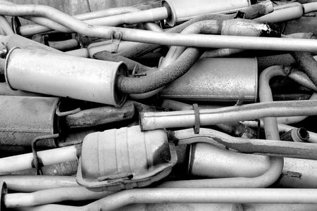 Pile of old exhaust pipes from cars. Black and white photo.