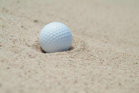 Golf-ball in bunker. Shallow depth of field.