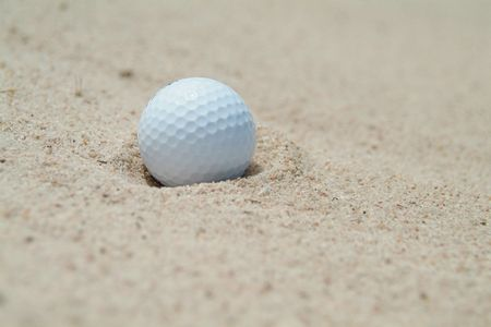 Golf-ball in bunker. Shallow depth of field.