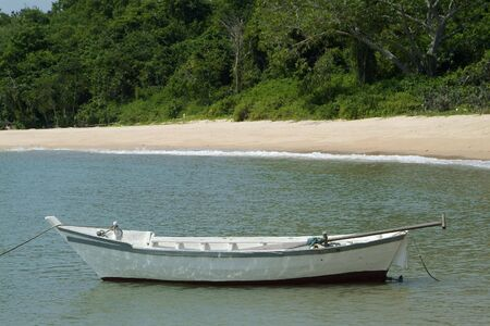 Small, white, wooden fishing boat near the beach in Chonburi province, Thailand Stock Photo - 496940