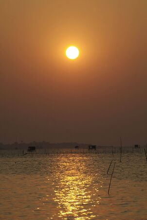 Golden sunset over Gulf of Siam seen from at Chonburi on Thailands eastern seaboard. Fishermans huts on stilts in the shallow water. photo