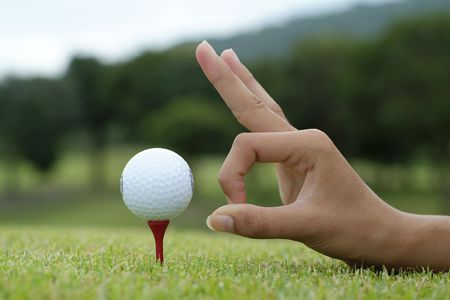 Hand and golf ball on tee Stock Photo