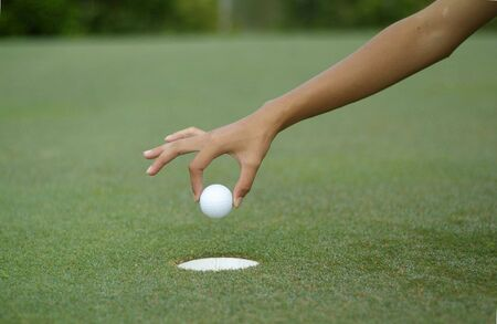Hand dropping a golf ball into the hole Stock Photo