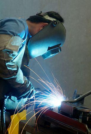 welding metal: Welder working on metal tubes Stock Photo
