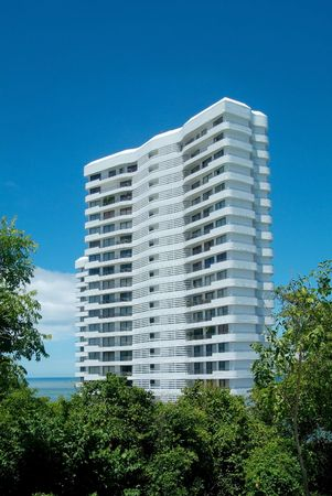 White apartment-building in a forest, near the sea