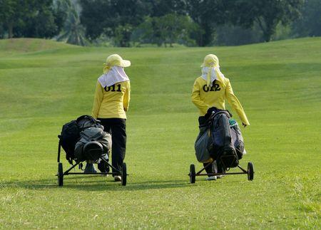 caddie: Two caddies walking down the fairway of a golf course in Thailand