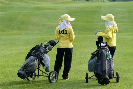 caddie: Two caddies, waiting on the fairway at a golf course in Thailand. Stock Photo