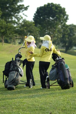 caddie: Two caddies at a golf course in Thailand